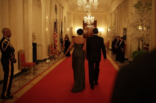 obama-with-michelle-walking-down-a-whitehouse-corridor-530x349