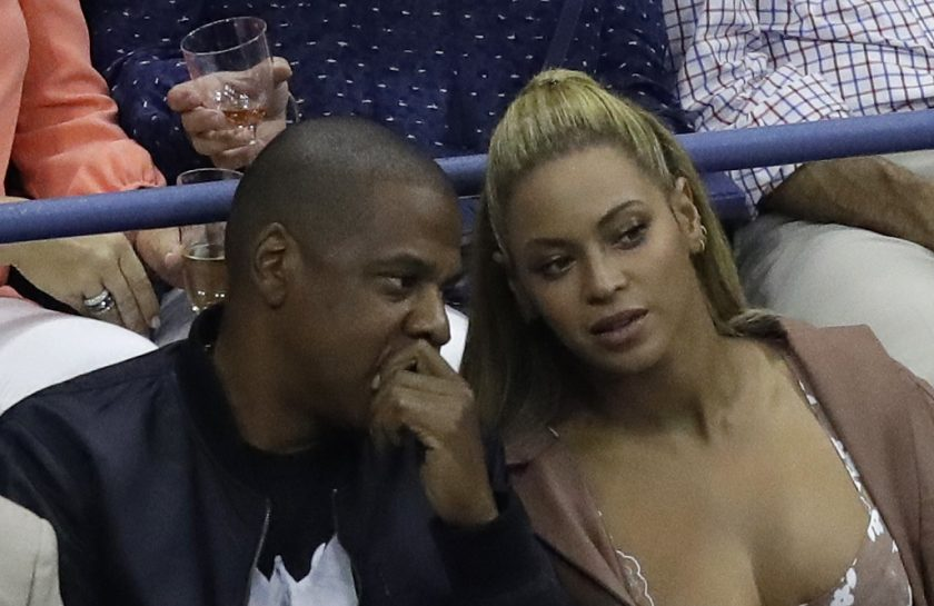 Music artists Jay Z, left, and Beyonce, talk while watching play between Serena Williams and Vania King, of the United States, during the second round of the U.S. Open tennis tournament, Thursday, Sept. 1, 2016, in New York. (AP Photo/Julio Cortez)